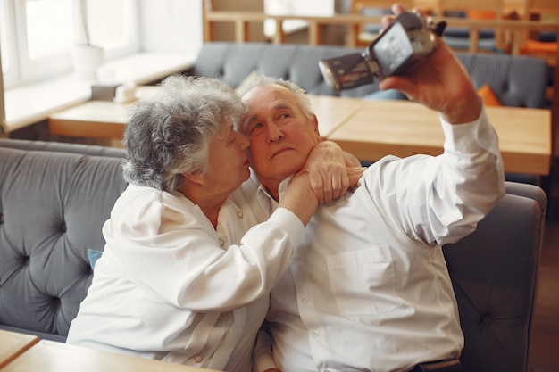 Elegante pareja de ancianos en un café con una cámara