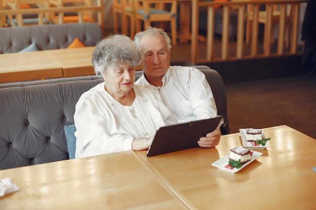 Elegante pareja de ancianos en un café con una tableta