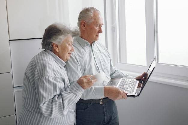 Elegante pareja de ancianos en casa usando una computadora portátil