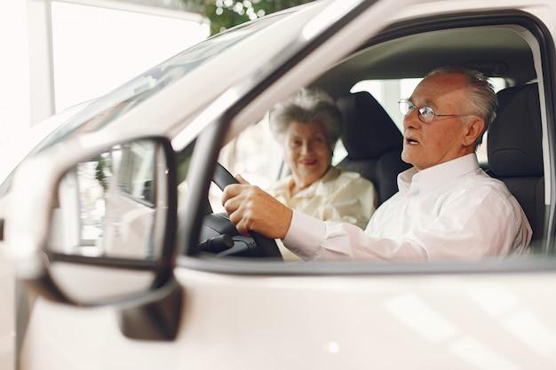 Elegante pareja de ancianos en un salón del automóvil