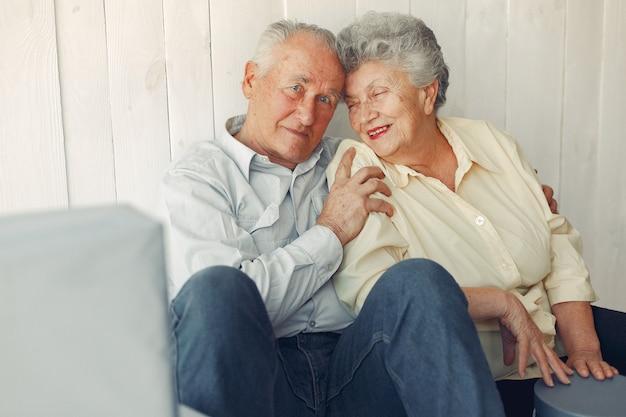 Elegante pareja de ancianos sentados en casa en un piso