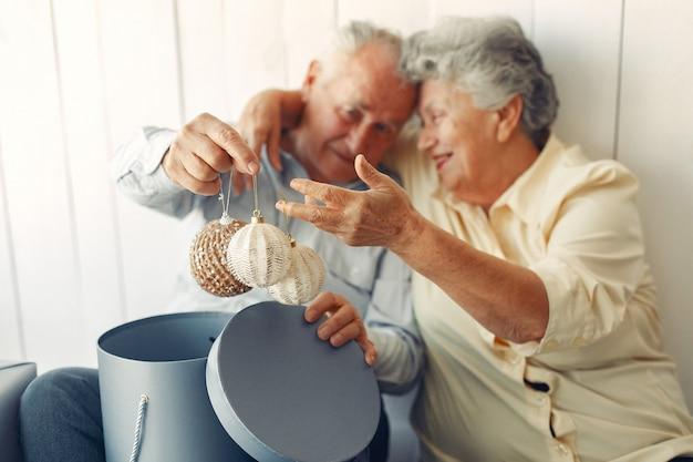 Elegante pareja de ancianos sentados en casa con regalos de navidad