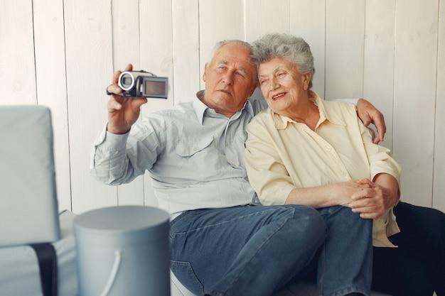 Elegante pareja de ancianos sentados en casa y usando una cámara