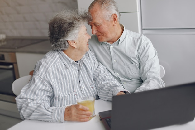 Elegante pareja de ancianos sentados en casa y usando una computadora portátil