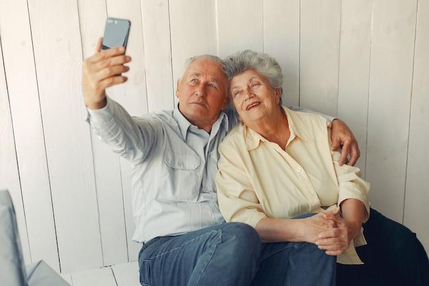 Elegante pareja de ancianos sentados en casa y usando un teléfono
