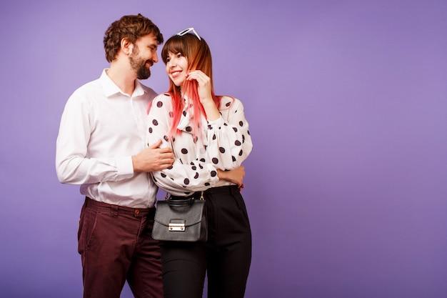 Elegante pareja de enamorados abrazándose y mirándose