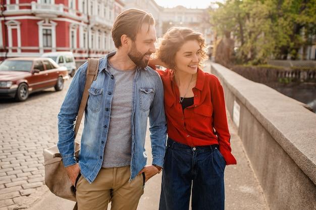 Elegante pareja de enamorados caminando abrazando en la calle en viaje romántico