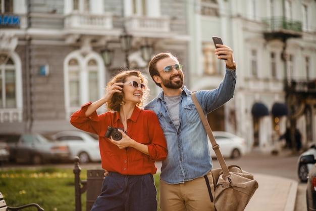 Elegante pareja de enamorados caminando abrazándose en la calle en un viaje romántico y tomando fotos