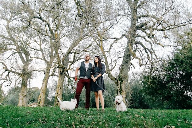 Elegante pareja de enamorados en el parque con sus dos perros blancos
