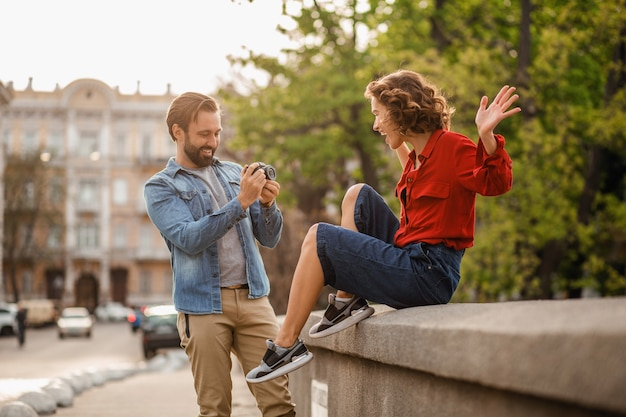Elegante pareja de enamorados sentados en la calle en viaje romántico, tomando fotos