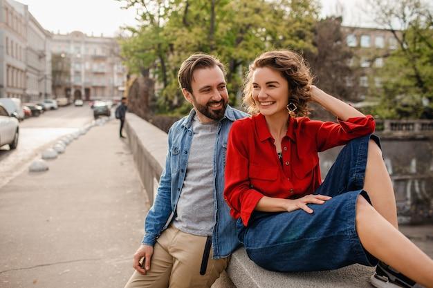 Elegante pareja de enamorados sentados en la calle en viaje romántico