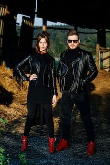 Elegante pareja glamorosa en chaquetas de cuero negro posando en un hangar