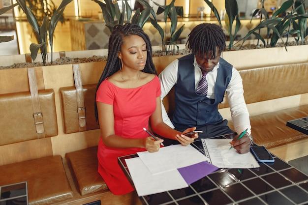 Elegante pareja negra sentada en un café y conversación de negocios