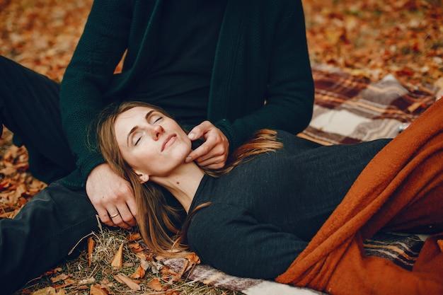Elegante pareja pasa tiempo en un parque de otoño