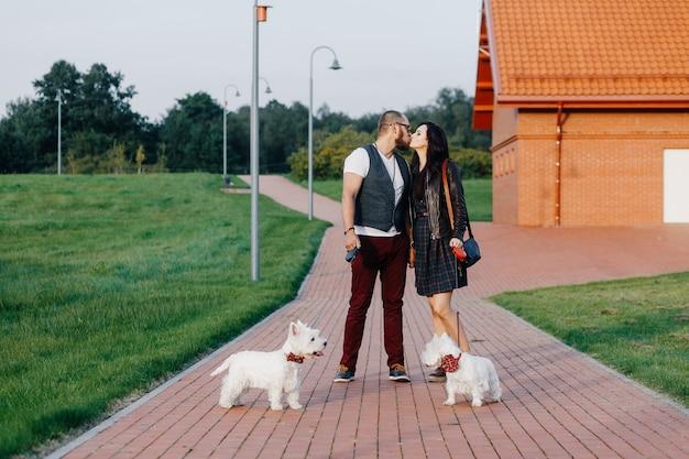 Una elegante pareja pasea por el parque con dos perros blancos