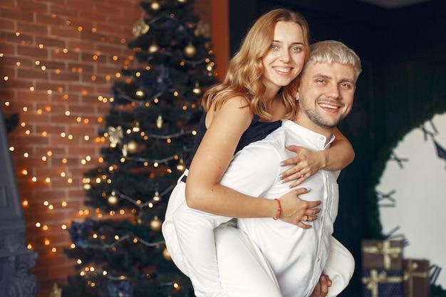 Elegante pareja de pie en casa cerca del árbol de navidad
