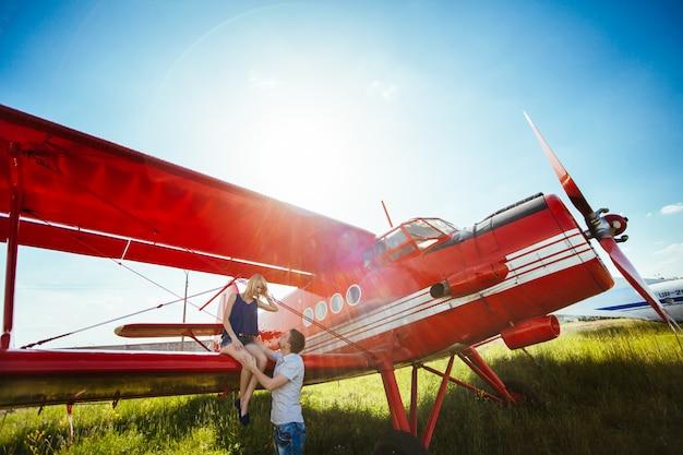 Elegante pareja de pie cerca de un avión en el aeropuerto. luna de miel