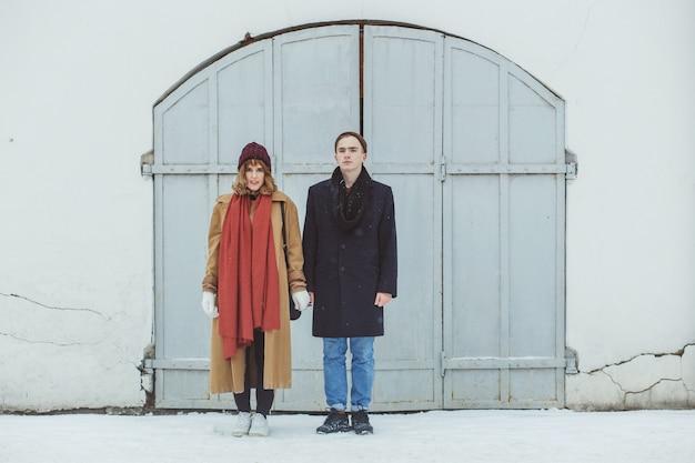 Elegante pareja de pie cerca del edificio histórico blanco