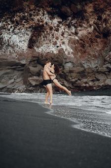 Elegante pareja en una playa cerca de rocas