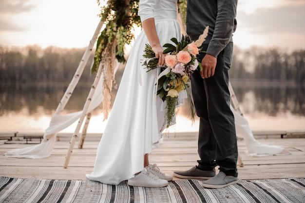 Elegante pareja de recién casados en calzado deportivo y ropa de boda en la orilla del río