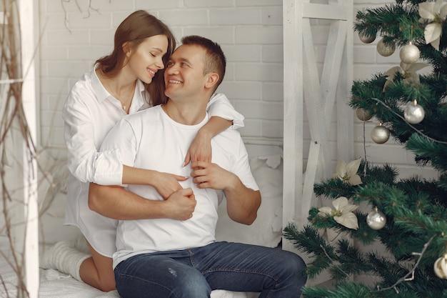 Elegante pareja sentada en una cama cerca del árbol de navidad