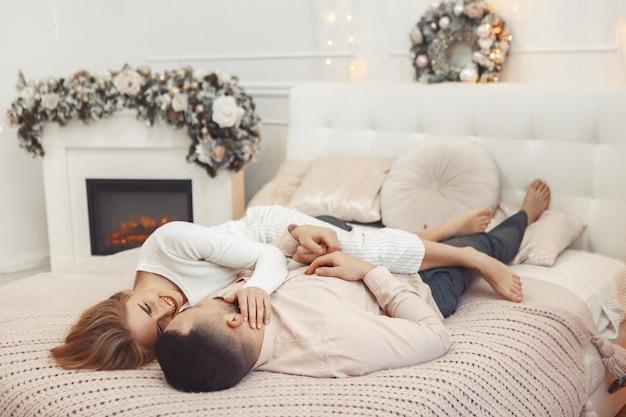 Elegante pareja sentada en una cama en una decoración navideña