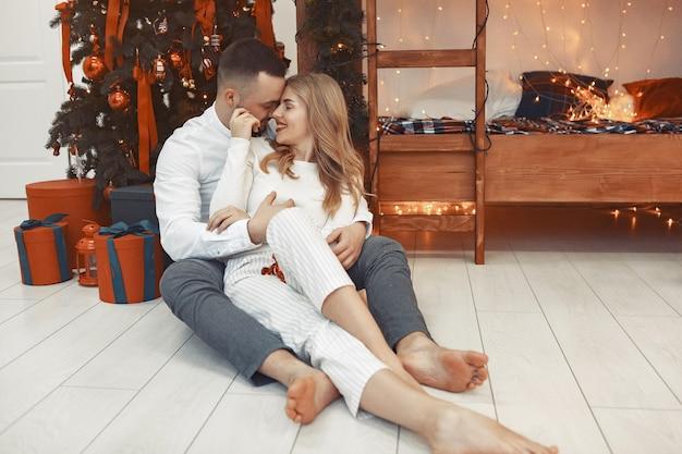Elegante pareja sentada en casa cerca del árbol de navidad