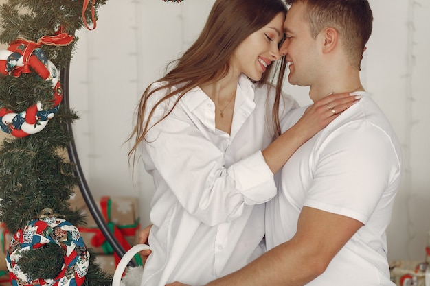 Elegante pareja sentada en casa cerca de regalos de navidad