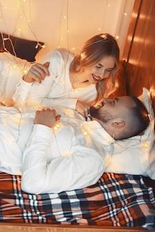 Elegante pareja sentada con una guirnalda en casa en una cama