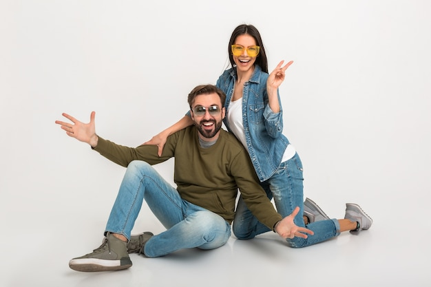 Elegante pareja sentada en el piso aislado, mujer y hombre muy sonrientes en jeans, con gafas de sol, divirtiéndose juntos, extendiendo las manos en emoción positiva