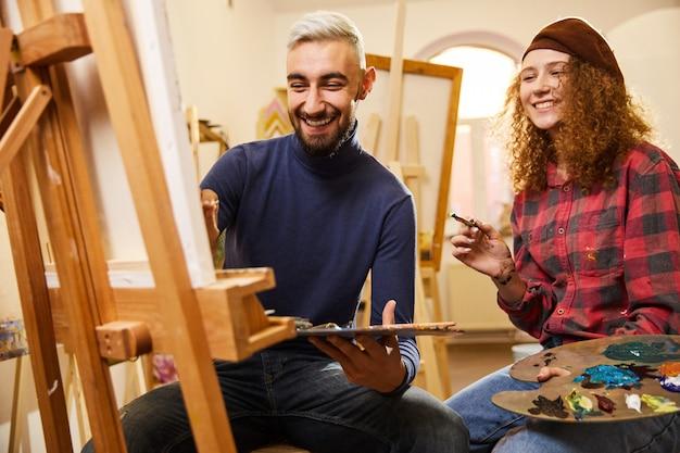 Elegante pareja sonriente dibujar una pintura