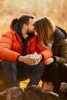 Elegante pareja con taza de café junto a la hoguera