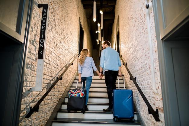 Elegante pareja de turistas tomados de la mano y tirando de las maletas, hombre y mujer en ropa casual, subir las escaleras, al llegar al hotel. viaje de negocios, vacaciones