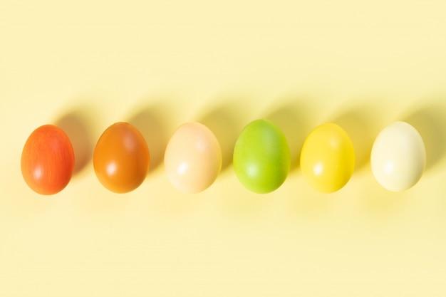 Elegante pascua plana pone, huevos de pascua sobre fondo amarillo