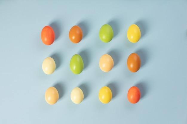 Elegante pascua plana pone, huevos de pascua sobre fondo azul.