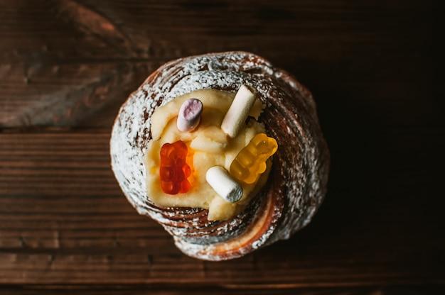 Elegante pastel de pascua con malvaviscos y ositos de gelatina sobre un fondo oscuro de madera rústica.