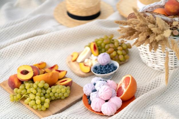Elegante picnic de verano sobre una manta blanca.