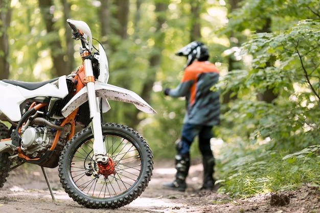Elegante piloto con moto estacionada en el bosque
