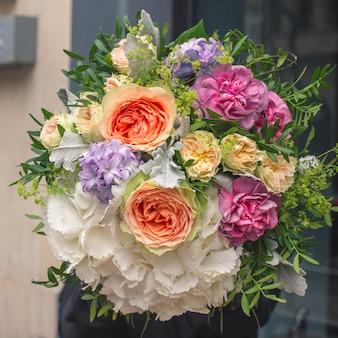 Un elegante ramo de flores blancas, naranjas, amarillas y moradas con hojas decorativas de color verde.