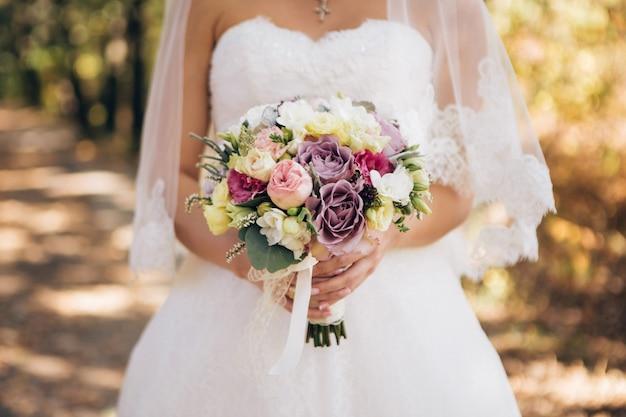 Elegante ramo de novia en manos de la novia. ramo con rosas lilas, blancas y rosas. ramo de novia en el bosque de otoño
