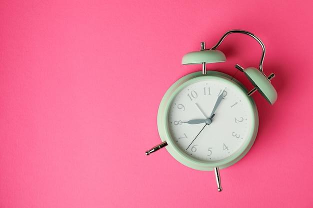 Elegante reloj despertador de menta en superficie rosa