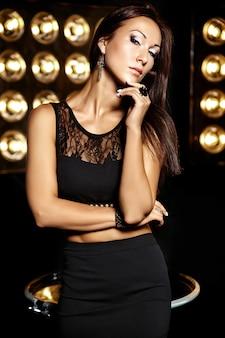 Elegante retrato de una bella modelo en ropa negra posando sobre fondo negro de luces de estudio