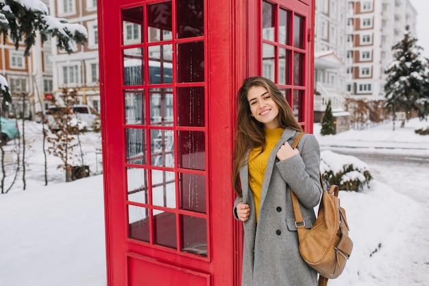 Elegante retrato británico de encantadora joven con cabello largo morena caminando en la calle cerca de la cabina de teléfono roja en la calle llena de nieve. tiempo de nieve fría, sonriendo, vacaciones de invierno, alegría.
