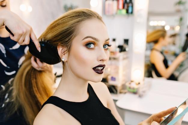 Elegante retrato de mujer joven atractiva en salón de belleza preparándose para la fiesta