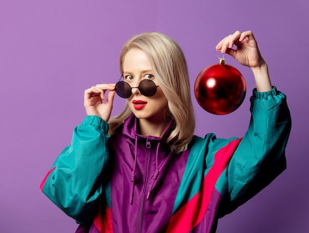 Elegante rubia en cazadora de los años 80 y gafas de sol roud sostiene adorno navideño en la pared púrpura