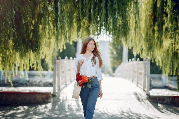 Elegante rubia en un parque de verano con flores.