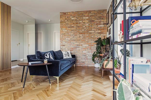 Elegante sala de estar escandinava con espacio abierto con sofá de diseño y estantería