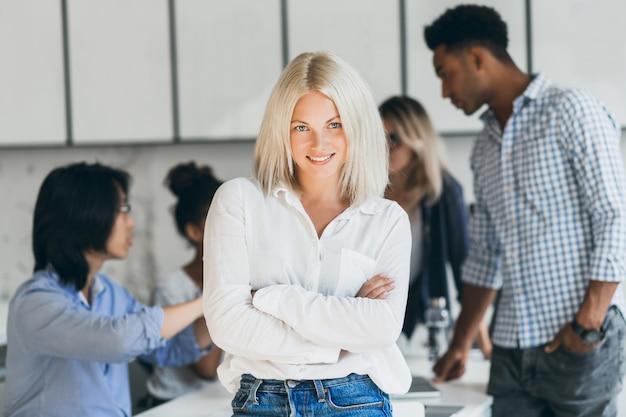 Elegante secretaria de pie en pose de confianza en la sala de conferencias y sonriendo. retrato interior de oficinista bastante rubia esperando negociación con socios.
