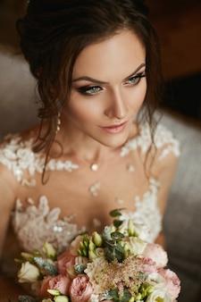 Elegante y sensual modelo morena con peinado de novia y maquillaje brillante en un elegante vestido de encaje con un ramo de flores en sus manos posando en el interior