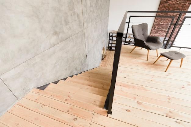 Elegante sillón moderno y taburete junto a la escalera